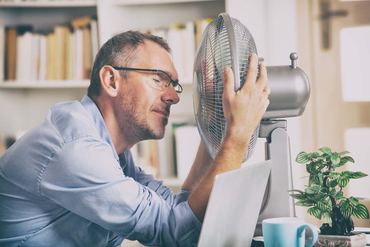 Man with his face in front of a fan
